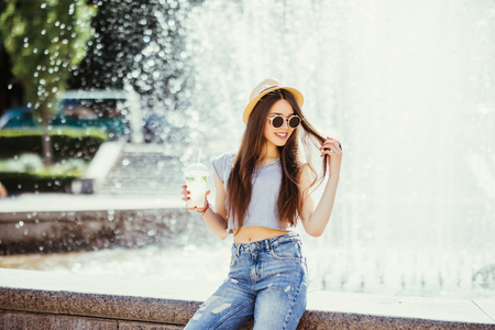 Summer sunny lifestyle fashion portrait of young stylish hipster woman walking on the street, wearing cute trendy outfit, drinking tasty smoothie, smiling enjoy her weekends, travel with backpack