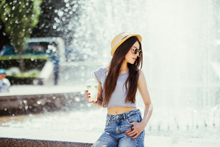 Smiling positive funny young woman holding cup drink, sunlight, outdoor, street style Zdjęcie Seryjne