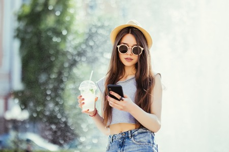 Young woman with mojito using mobile phone on the summer street
