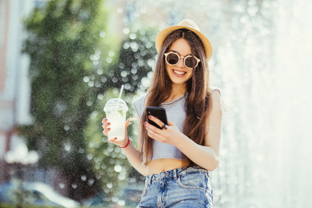 Young woman in summer outfit drink cocktails outdoors typing on phone near fountain Stock Photo