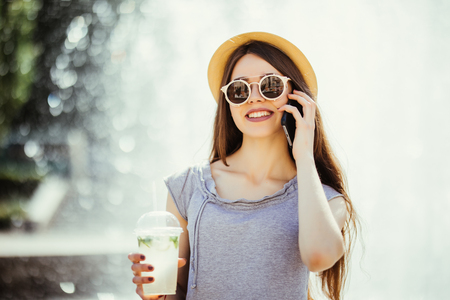 Beautiful young woman drinking mojito delicious refreshing cocktail on sunny day in the street and talking phone. Fresh juice. Woman relaxing on a summer day. Mobile device. Smart phone Stock Photo