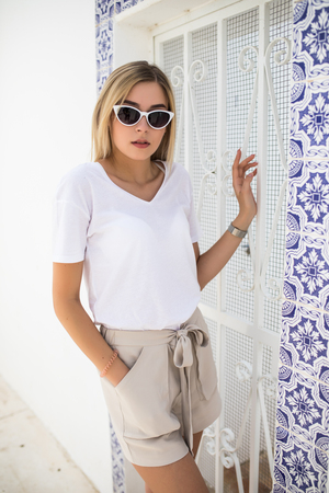 Beautiful young woman standing at the wall covered with portuguese traditional tiles azulejo.