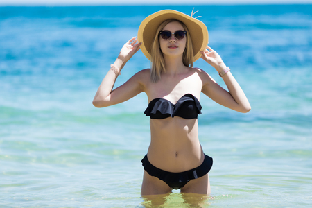 Young pretty woman walking in ocean water at beach