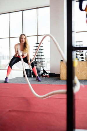 Battle ropes session. Attractive young fit and toned sportswoman working out in functional training gym doing crossfit exercise with battle ropes copyspace battling ropes cross-fit workout motivation Stock Photo