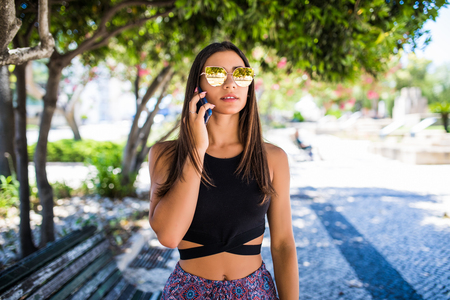 Beautiful woman talking on cell phone in the park