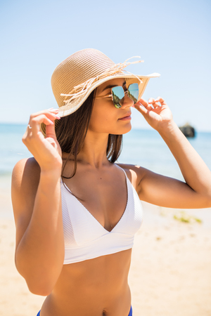 Stylish woman in straw hat and sunglasseson the beach on a sunny day