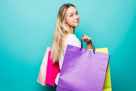 Portrait of excited beautiful girl holding shopping bags isolated over blue background