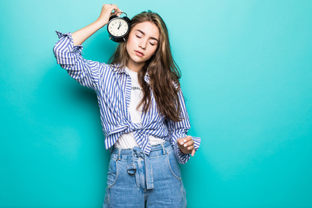 Young woman with alarm clock on blue background.