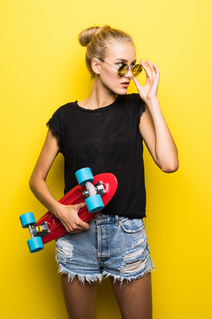 Fashion happy smiling hipster cool girl in sunglasses and colorful clothes with skateboard having fun outdoors against the orange background