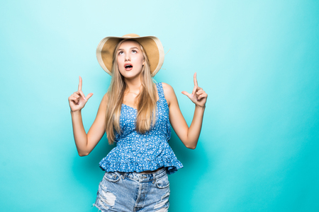 Portrait of smiling young woman in straw summer hat, orange glasses pointing index fingers up on copy space isolated on yellow background. People sincere emotions, lifestyle concept. Advertising area