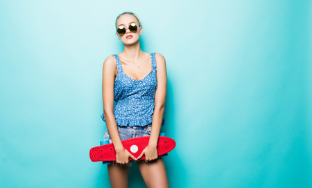 Attractive girl hold skateboard in hat and sunglasses posing on blue background.