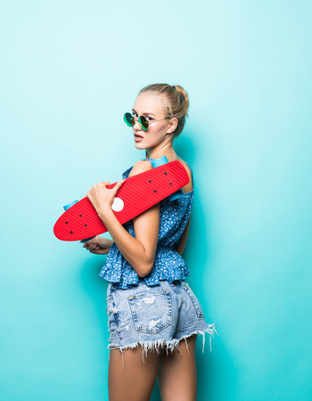 Feeling free and happy. Attractive young woman smiling and carrying skateboard while standing against blue background Stock Photo