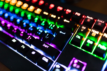 Gamer keyboard with colorful lights, modern laptop computer.