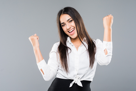 Successful businesswoman with arms up over a white background