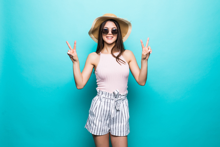 Portrait of a happy girl in summer hat showing peace gesture with two hands isolated over blue background