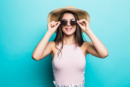 Portrait of pretty woman in sunglasses and hat over blue colorful Stock Photo