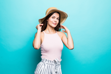 Happy thinking young woman looking up in straw hat on blue background
