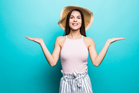 Shrugging woman in doubt doing shrug showing open palms, gesturing, look to side on blue background Stock Photo