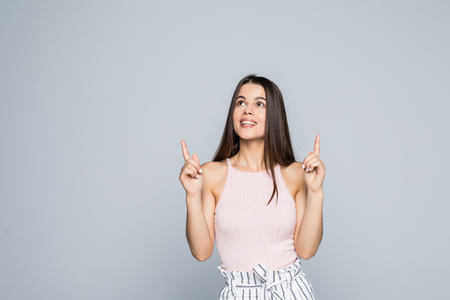 Beautiful woman student raising hands high and pointing up with index fingers on gray background Stock Photo