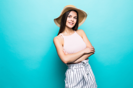 Portrait of a smiling young woman standing with arms folded and looking away at copyspace isolated over blue background