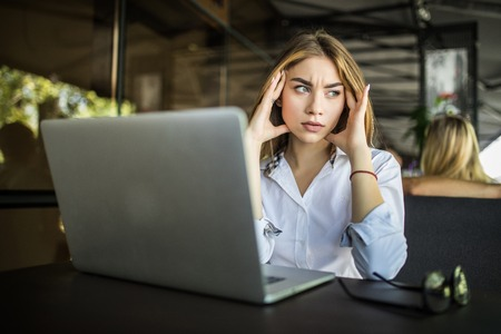 Stressed female student having headache touching temples preparing for test in cafe, frustrated millennial girl feels nervous or tired, afraid of exam failure, suffering from anxiety or panic attack