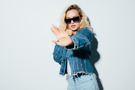 Image of a young woman wearing sunglasses dressed in jeans jacket standing isolated over white background make stop gesture.