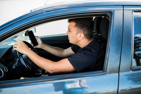 Man sitting in car with mobile phone in hand texting while driving. Distracted shocked guy checking his smart phone not paying attention at road annoyed by bad text message email outdoors background Imagens