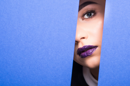 Face of young beautiful girl with a bright make-up looks through a hole in violet paper. Stock Photo