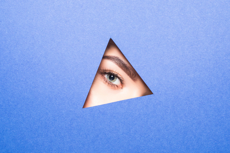 A girl with beautiful bright eyes with shadows and expressive eyebrows looks into the hole of colored purple paper.
