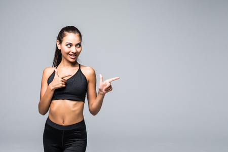 Portrait of a happy young sports girl pointing two fingers up at copy space isolated over gray background