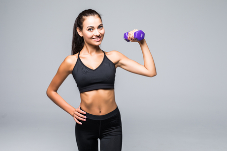 Beautiful young woman doing exercises with dumbbells at biceps.