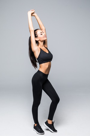 Full length portrait of happy young woman with arms raised doing stretching exercise against white background