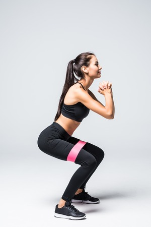 donna bionda sottile facendo squat con fascia fitness loop isolato su priorità bassa bianca