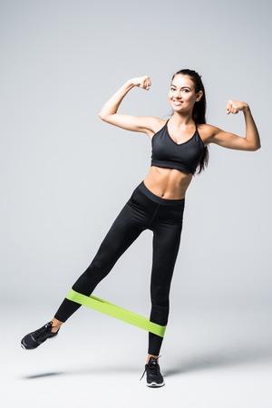 Mujer haciendo ejercicio haciendo ejercicio para piernas con bandas elásticas sobre fondo blanco.