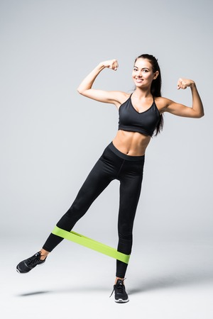 Woman exercising doing workout for legs with elastic bands on white background