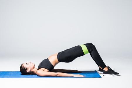 Donna che si esercita facendo allenamento per le gambe con elastici sdraiati sul pavimento su sfondo bianco