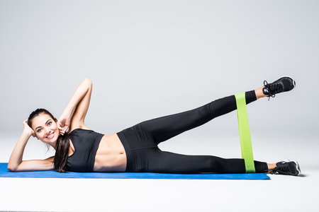Woman exercising doing workout for legs with elastic bands lying on floor on white background