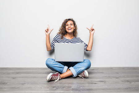 Portrait of satisfied woman with beautiful smile with laptop and sitting in lotus pose on the floor over grey wall