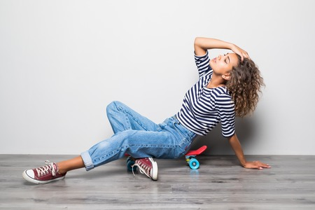 Young mixed raced girl sitting on cruiserboard sitting on floor isolated on white.
