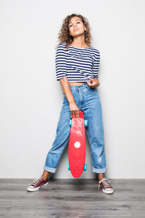 Stunning young woman with curly hair in jeans and shirt holding skateboard with sincere smile on white