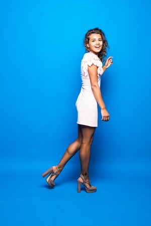 Portrait of gorgeous woman with curly brown hair expressing joy and delight while posing in elegant dress isolated over blue background 免版税图像