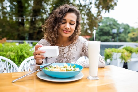 Close up of young attractive woman eating salad at street cafe.