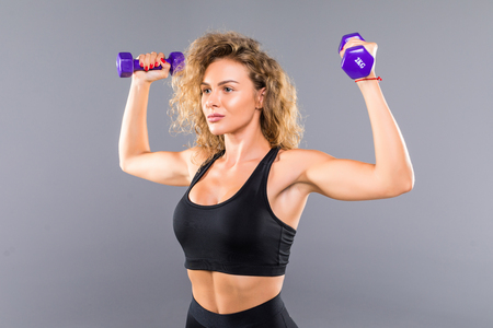Photo of slim sporty woman doing exercises with small dumbbells isolated over gray background