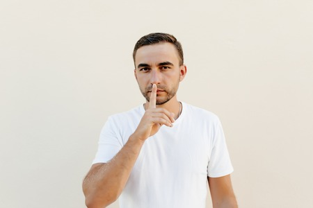 Secret, gossip concept. Young man whispering a secret behind his hand isolated on trendy orange studio background. Human emotions, facial expression concept.