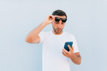 Young man gasping, shocked and appalled by a message he receives, blue background Reklamní fotografie