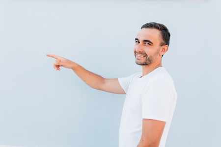 Closeup side view portrait of young man, laughing, pointing with finger at someone or something, isolated on blue background.