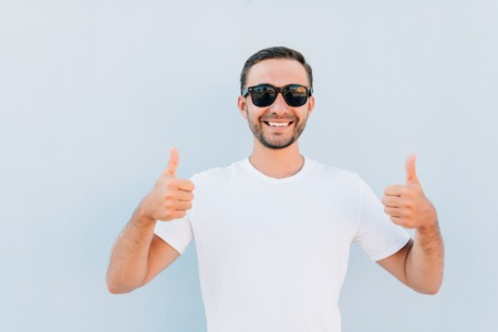 Smiling young guy in sunglasses showing thumbs up gesture isolated over blue background. Looking at camera.