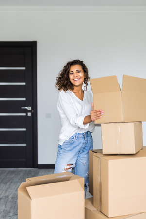 Happy smiling woman carrying carton boxes moving