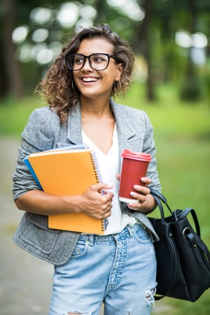 Portrait of attractive mixed race woman student in eyesglasses with coffee to go and textbook in hands and looking at camera. Stock Photo