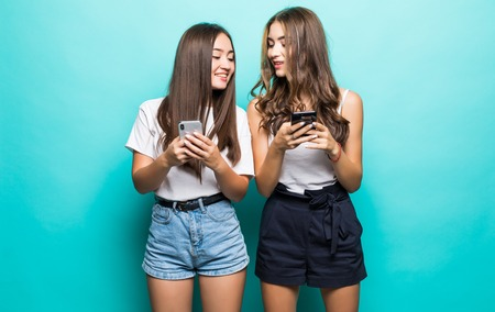 Two multiethnic women both using cell phones isolated over blue background Фото со стока